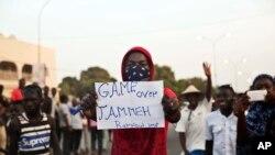 """Un homme brandit une affiche avec inscription : """"C'est fini pour Yahya Jammeh !"""" au milieu des manifestants en liesse à Serrekunda, Gambie, 19 janvier 2017."""