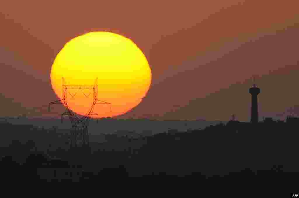 The sun sets behind an electric piler near Saint-Félix-Lauragais, southwestern France, Aug. 30, 2015.