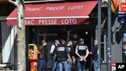 Police officers investigate after a man wielding a knife attacked residents venturing out to shop in the town in Romans-sur-Isere, southern France, April 4, 2020.