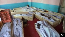 FILE - Bodies of civilians and security forces are placed at a hospital in Ghazni province, west of Kabul, Afghanistan, Aug. 12, 2018.