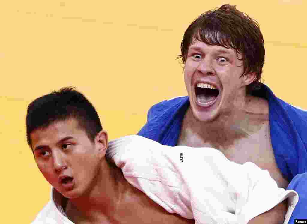 El ruso Ivan Nifontov (de azul) celebra después de derrotar al japonés Takahiro Nakai (de blanco), luego de derrotarlo en judo masculino de menos de 81 kilos.