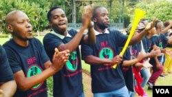 Gli attivisti cantano durante una manifestazione in un parco di Pretoria chiedendo un intervento più veloce su restituzione delle terre. (A. Powell / VOA)