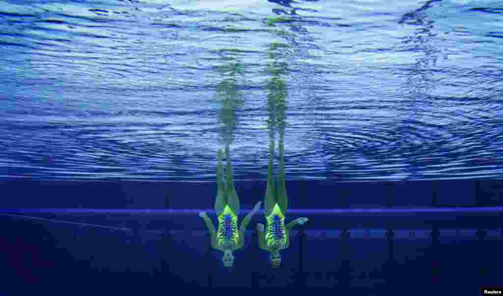 Italy's Giulia Lapi and Mariangela Perrupato perform underwater in the synchronised swimming duets technical routine qualification round.