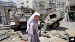 Seorang warga Palestina berjalan di dekat kendaraan militer Israel yang rusak di Khan Younis, Jalur Gaza Selatan (11/8).