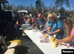 Catholic Church volunteers serve lunch to people affected by Hurricane Michael, in Callaway, Fla., Oct. 13, 2018.