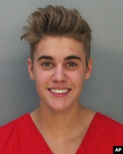 This police booking mug made available by the Miami Dade County Corrections Department shows pop star Justin Bieber, Jan. 23, 2014.