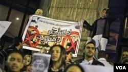Beberapa demonstran oposisi unjuk rasa membawa poster bergambar Presiden Hosni Mubarak dan puteranya, Gamal Mubarak di Kairo, Mesir.