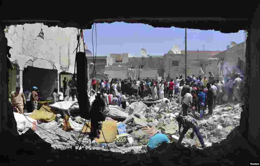 Men search for survivors amid debris of collapsed buildings after what activists said was an air raid by forces loyal to Syria's President Bashar al-Assad in Raqqa province, eastern Syria.