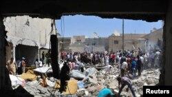 Warga mencari korban selamat di antara reruntuhan bangunan setelah sebuah serangan udara yang diduga diluncurkan oleh pasukan pemerintah Suriah (10/8).