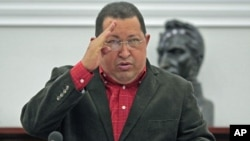 Venezuela's President Hugo Chavez salutes during the Council of Ministers at Miraflores Palace in Caracas, February 23, 2012.
