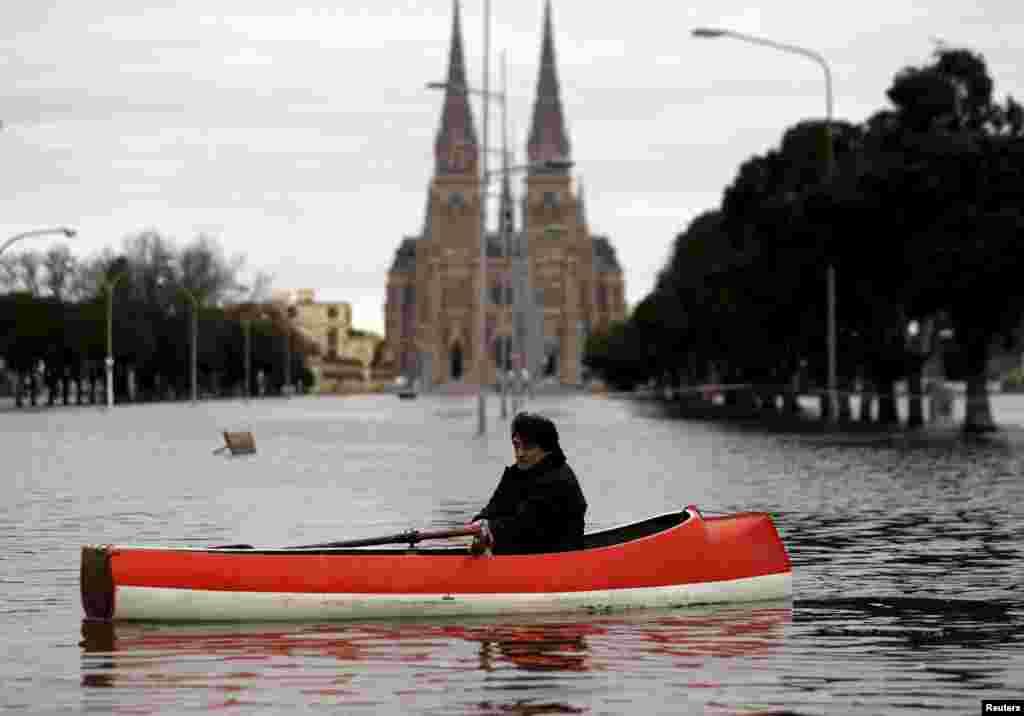 បុរសម្នាក់ចែវទូកនៅវិថីជន់លិចមួយនៅខាងមុខវិហារ Basilica of Lujan ជិតក្រុង Buenos Aires ប្រទេសអាហ្សង់ទីននាថ្ងៃទី ១២ ខែសីហា ឆ្នាំ២០១៥។
