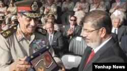 이집트 수도 카이로의 한 군사기지에서 열린 기념식에서 탄타위(좌측) 국방장관으로부터 최고 무공훈장인 '군의 방패'를 받고 있는 무함마드 무르시 대통령(자료사진)