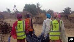 Les secouristes portent le corps d'une victime suite à un attentat-suicide à Maiduguri, au Nigeria, le 2 avril 2018.
