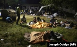 People displaced from their earthquake destroyed homes spend the night outdoors in a grassy area that is part of a hospital in Les Cayes, Haiti, late Saturday, Aug. 14, 2021.