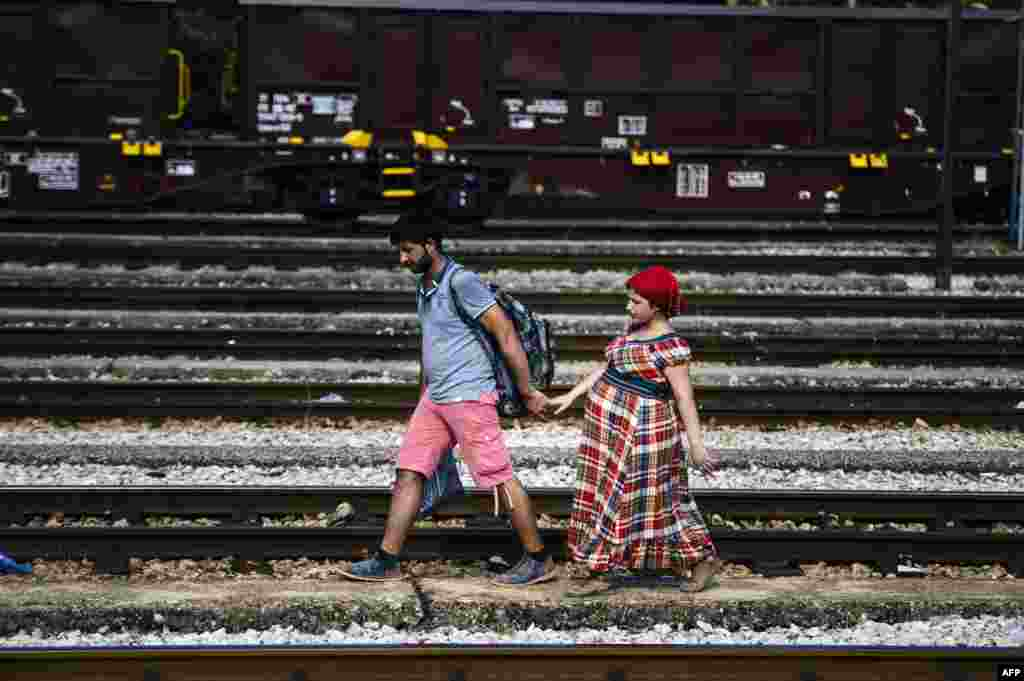 A Syrian migrant and his pregnant wife walk on train tracks towards the town of Gevgelija on the Macedonian-Greek border to catch a train to Serbia and the North European countries, July 27, 2015.