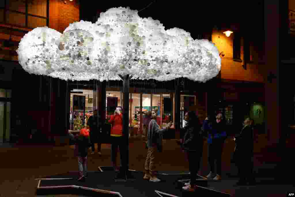 Visitors admire the artwork 'Cloud', formed from 6,000 incandescent light bulbs, during a rehearsal for 'Lumiere Durham' light festival in the British city of Durham on November 13, 2019.