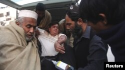 Seorang sopir yang terluka (berbaju putih) selamat dari penembakan yang dilancarkan oleh sekelompok bersenjata di Swabi, tiba di rumah sakit Lady Reading di Peshawar, Pakistan (1/1).