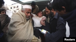 An injured driver (in white) who survived a shooting by unidentified gunmen in Swabi, arrives at the Lady Reading Hospital in Peshawar, January 1, 2013.