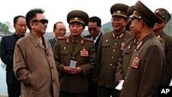 ທ່ານ Kim Jong Il ຜູ້ນໍາເກົາຫຼີເໜືອ ທີ 2 ຈາກຊ້າຍໃສ່ແວ່ນຕາ ເວົ້າກັບພວກນາຍພົນທະຫານຈຸນຶ່ງ ເວລາໄປຢ້ຽມຢາມຟາມຂອງກອງ ທັບແຫ່ງນຶ່ງ ໃນເກົາຫລີເໜືອ