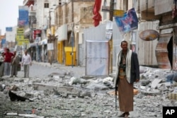 FILE - A Shiite fighter known as a Houthi stands guard in front of buildings destroyed by a Saudi-led airstrike in Sana'a, Sept. 5, 2015.