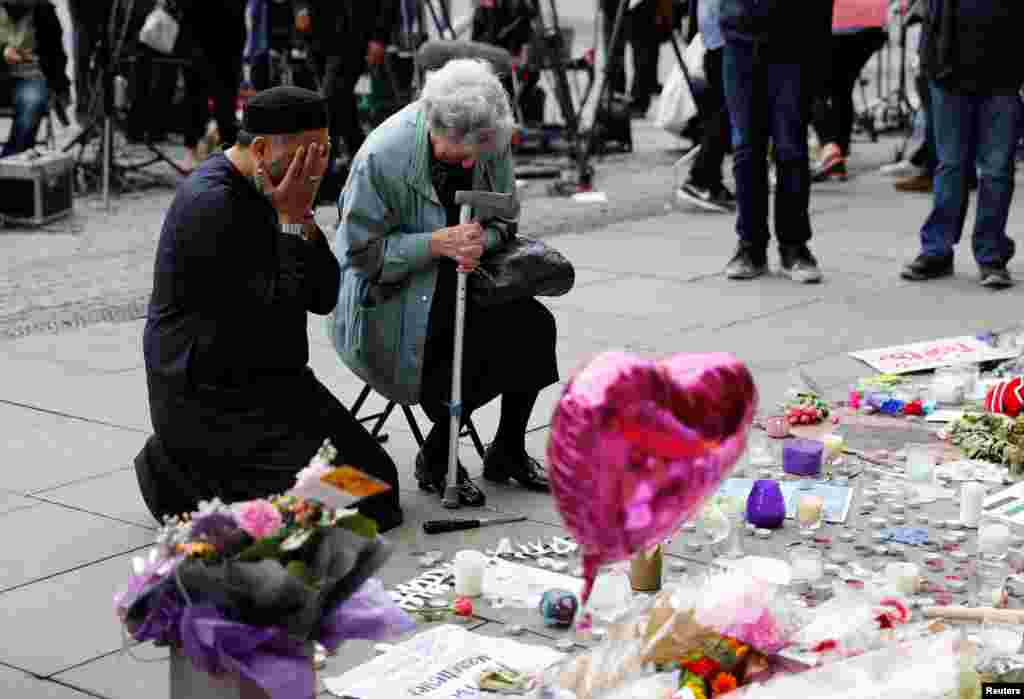 A Jewish woman named Renee Rachel Black and a Muslim man named Sadiq Patel react next to floral tributes for the victims of the deadly Manchester concert suicide bombing, at St. Ann's Square in Manchester, Britain.