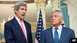 Secretary of State John Kerry (L), joined by Defense Secretary Chuck Hagel, speaks to media at the State Department in Washington, Oct. 24, 2014.