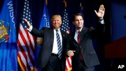 FILE - Governor Scott Walker winks as he walks offstage after introducing then-Republican presidential candidate Donald Trump at a campaign rally at the University of Wisconsin campus in Eau Claire, Nov. 1, 2016.
