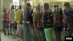 Residents of the reception center for migrants and asylum-seekers in Traiskirchen, Austria, are seen lining up for food at the camp's kitchen. (Photo - VOA video grab)