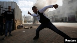FILE - A young Palestinian protester throws stones at Israeli troops during clashes following an anti-Israel demonstration in solidarity with al-Aqsa mosque, in the West Bank city of Hebron, Nov. 14, 2014.