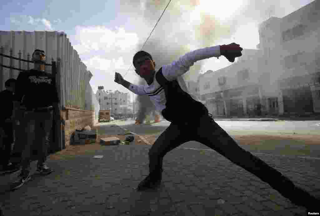 A young Palestinian protester throws stones at Israeli troops during clashes following an anti-Israel demonstration in solidarity with al-Aqsa mosque, in the West Bank city of Hebron, Nov. 14, 2014.