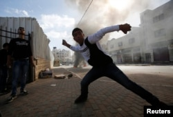 FILE - A Palestinian youth throws stones at Israeli troops following an anti-Israel demonstration in solidarity with al-Aqsa mosque in the West Bank city of Hebron, Nov. 14, 2014.