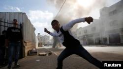 지난해 11월 요르단 서안지구 헤브론에서 팔레스타인 시위대 청년이 이스라엘 경찰을 향해 돌을 던지고 있다.