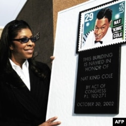 Singer Natalie Cole looks at a mock stamp and plaque following the renaming of a post office for her father