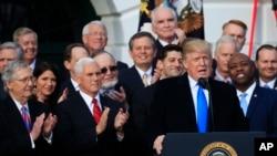El presidente de EE.UU., Donald Trump, acompañado del vicepresidente Mike Pence (segundo desde la derecha) y los legisladores de la mayoría republicana en el Congreso, celebran la aprobación de la reforma a la ley de impuestos, la mayor victoria del gobierno de Trump.
