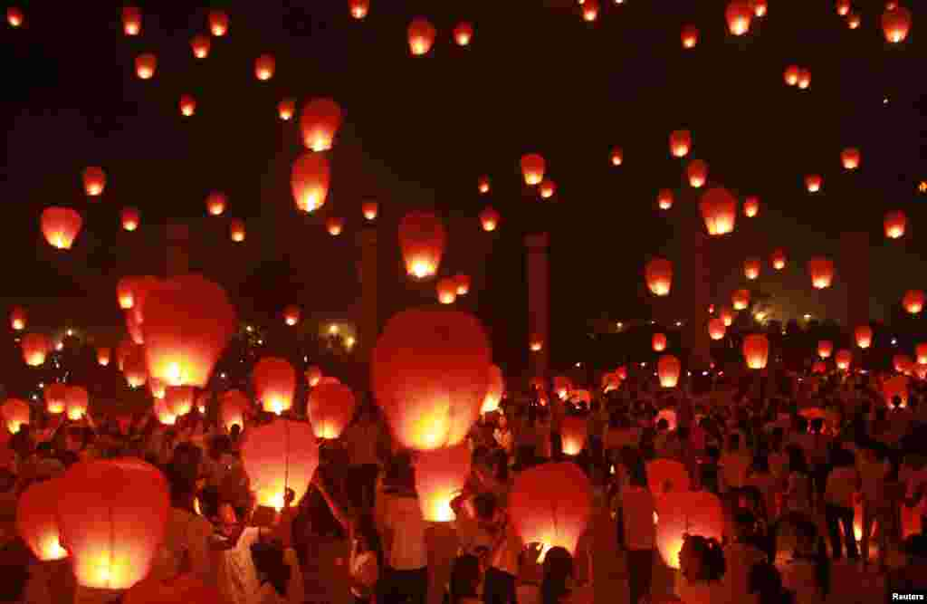People release paper lanterns ahead of the Mid-Autumn Festival in Yichun, Jiangxi province, China, Sept.7, 2014.