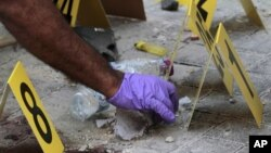 Policemen collect evidence at scene of deadly explosion in Manama, Bahrain, Nov. 5, 2012.