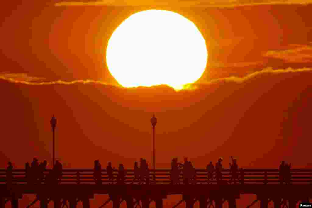 The sun sets behind a cloud as people cool off with a walk along an ocean pier in Oceanside, California, U.S. July 5, 2018