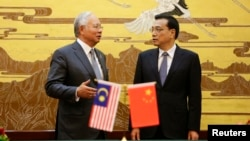 Malaysia's Prime Minister Najib Razak (L) speaks to China's Premier Li Keqiang during a signing ceremony at the Great Hall of the People, in Beijing, May 29, 2014.