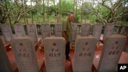 War veteran Duong Van Dau walks in between a row of headstones at a memorial for North Korean fallen pilots in Bac Giang province, Vietnam, Feb. 16, 2019.