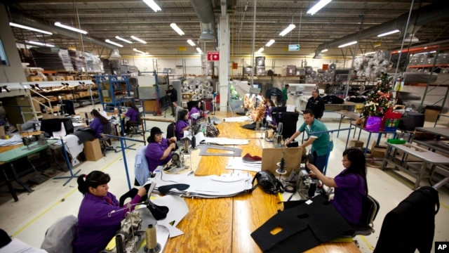 In this Friday, Dec.27, 2013 photo, workers manufacture car dash mats at a maquiladora belonging to the TECMA group in Ciudad Juarez, Mexico.