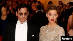 """Actor Johnny Depp and his fiancee, model Amber Heard, arrive at the Metropolitan Museum of Art Costume Institute Gala Benefit celebrating the opening of """"Charles James: Beyond Fashion"""" in Upper Manhattan, New York, May 5, 2014. REUTERS/Lucas Jackson (UN"""