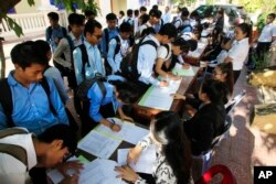 FILE - Students register to participate in a campaign by the National Election Committee, NEC, in Phnom Penh, Cambodia, Wednesday, May 9, 2018.