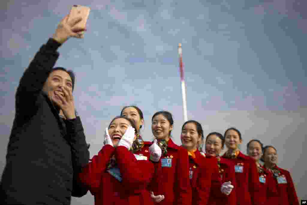 Hospitality staff members pose for a selfie during the opening session of China's National People's Congress (NPC) at the Great Hall of the People in Beijing.