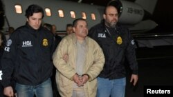 "FILE - Mexico's top drug lord Joaquin ""El Chapo"" Guzman is escorted as he arrives at Long Island MacArthur airport in New York after his extradition from Mexico, Jan. 19, 2017."