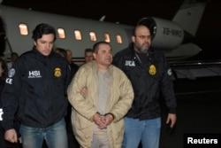"FILE - Mexico's top drug lord Joaquin ""El Chapo"" Guzman is escorted as he arrives at Long Island MacArthur Airport in New York, U.S., Jan. 19, 2017, after his extradition from Mexico."