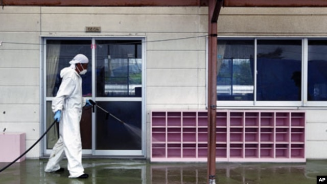A worker decontaminates radiation from the exterior of Yasawa Kindergarten in Minami-Soma, about 12 miles (20 kilometers) away from the tsunami-crippled Fukushima Dai-ichi nuclear facility, in Fukushima prefecture, northeastern Japan,  August 18, 2011