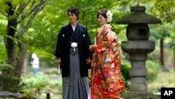 Pasangan pengantin Jepang yang mengenakan baju kimono tradisional berfoto di taman Hibiya, Tokyo.