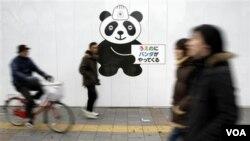 Warga Tokyo melintasi pengumuman kedatangan panda di kebun bintang Ueno, Jumat (2/18). Sepasang panda dari Tiongkok tiba di Ueno, Senin malam.