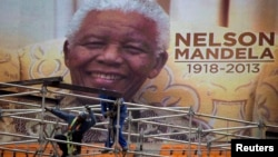 An image of Nelson Mandela is displayed on a digital screen as workers on scaffolding construct a stage ahead of Mandela's national memorial service at First National Bank (FNB) Stadium, also known as Soccer City, in Johannesburg, Dec. 9, 2013.