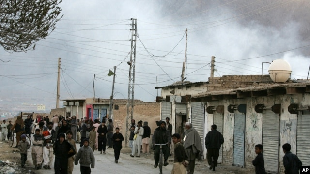 Local residents gather at a road as smoke rise from the site of a bomb blast in a market in Quetta, Pakistan, Feb. 16, 2013.